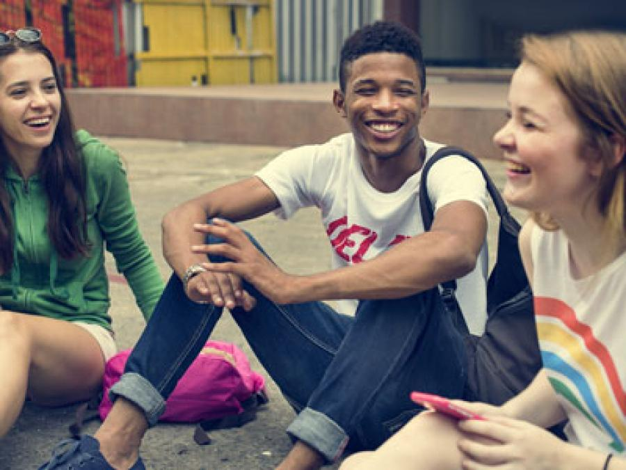 3 teenagers sitting on the ground and laughing together.